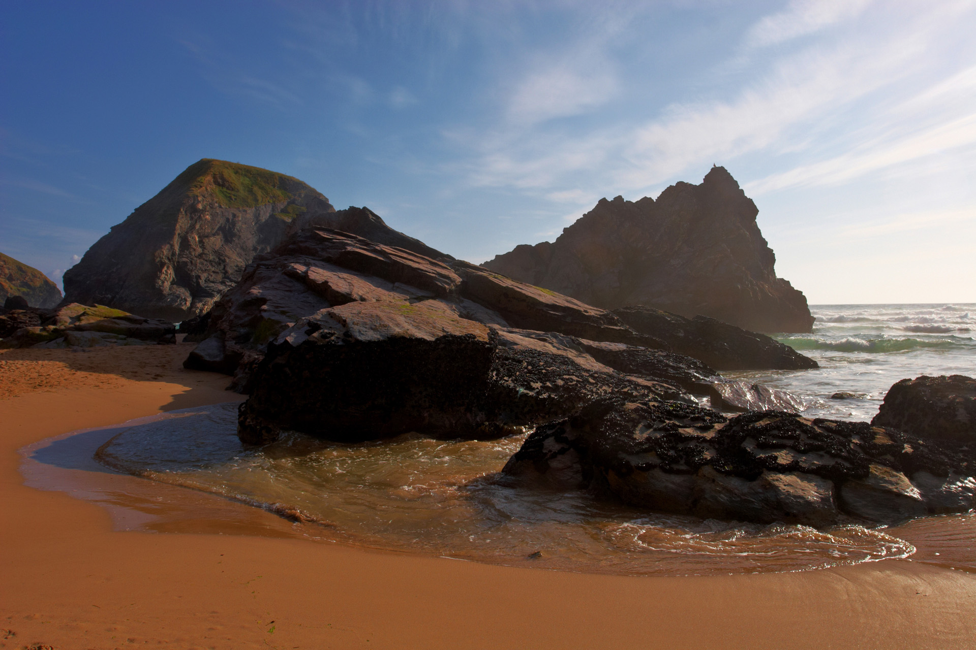 Rock formations in the wet sand at Bedruthan Steps