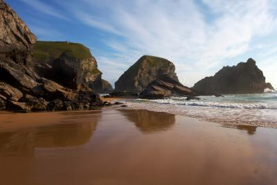 Reflections of rock formations in the wet sand at Bedruthan Step